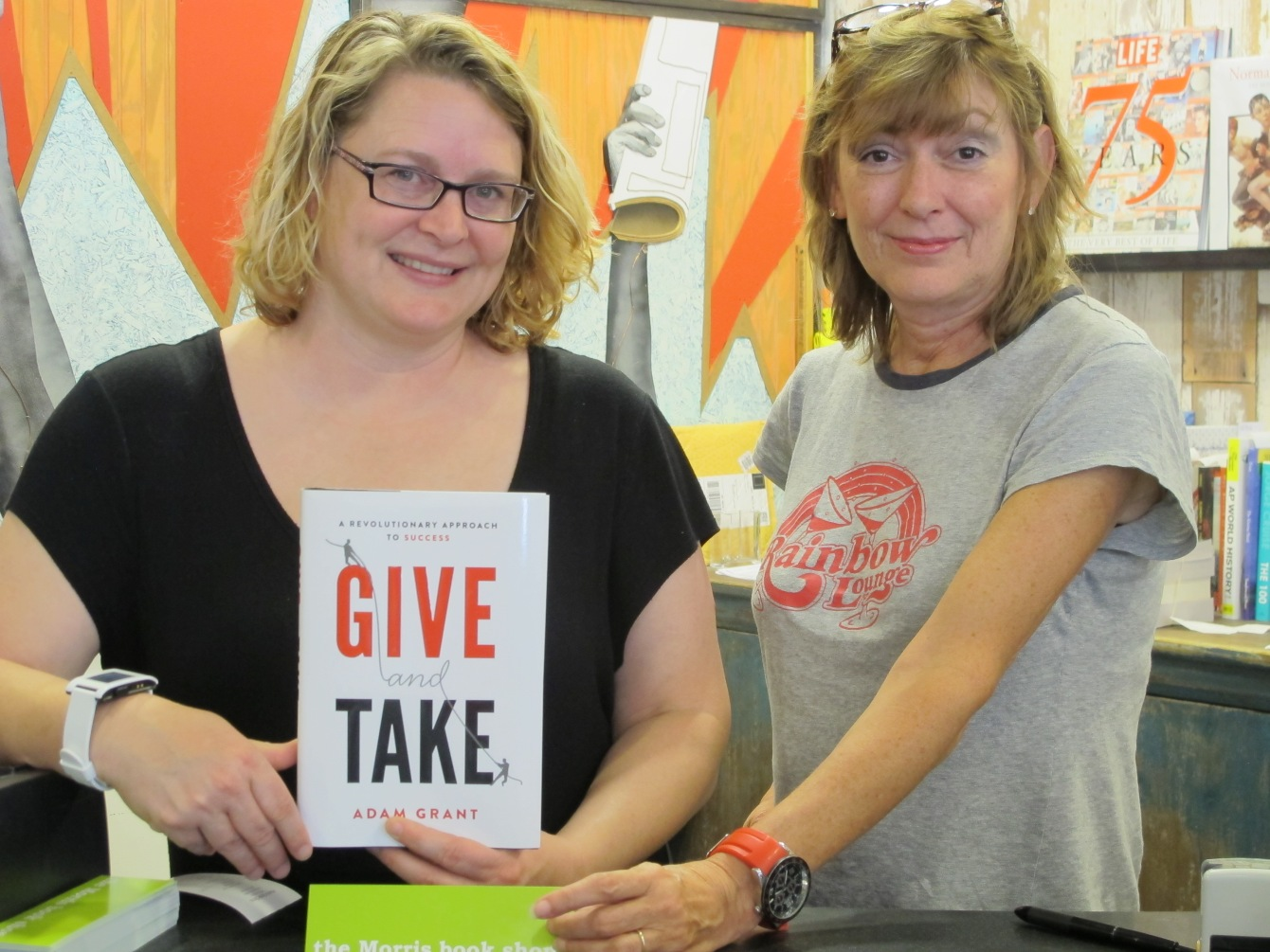"Two proud employees at Morris Book Shop in Lexington, KY sells a copy of Adam Grant's ""Give and Take"" to Anna Seacat of Socially Minded Marketing."